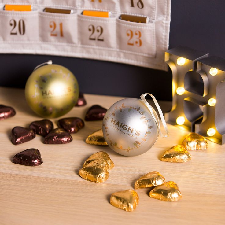 Silver and gold bauble tins filled with delicious premium Haigh's chocolate hearts. Perfect to hang on the Christmas tree and a popular collect each year.