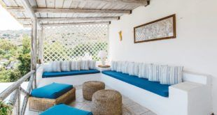 GREEK STYLE VILLAS -  White stone seating with blue cushions.