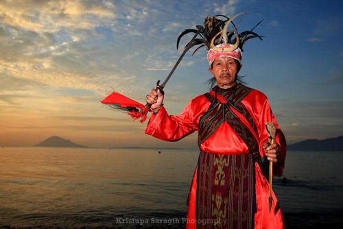 Penari cakalele yang membuka iring-iringan rombongan pelaksana upacara gocefa di Pantai Malalayang dengan latar belakang Pulau Manado Tua, Jumat (27/05). Foto oleh Kristupa Saragih