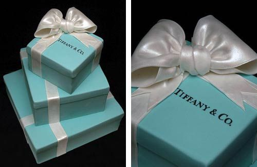 Three tier blue and white square Tiffany box cake made to look like three gift boxes, one on top of the other. Decorated with white satin ribbons with the perfect white bow as the wedding cake topper. The top tier has the Tiffany & Co. company logo written in black, just like a Tiffany jewellery box.