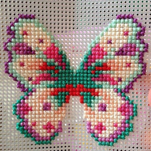 Mariposa bordada en punto de cruz en malla plastica.