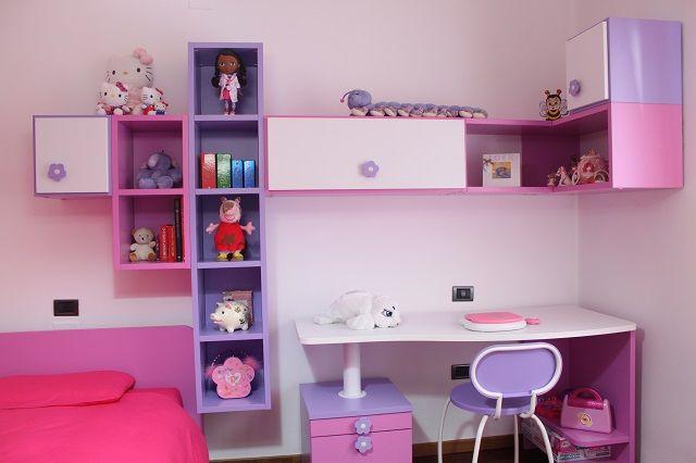 Angolo studio con scrivania sagomata e libreria con vani a giorno e chiusi.