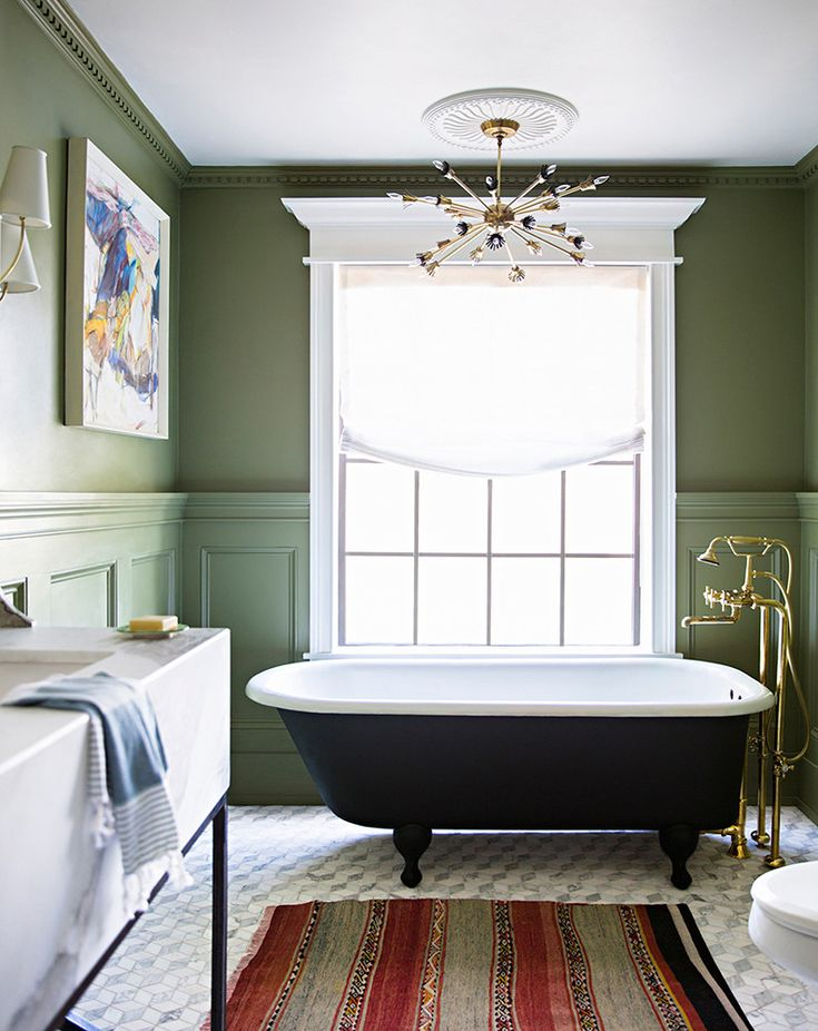 The light fixture, claw-foot tub, and creamy green on the walls are the right combo in this space.   TIP: Throw in a nice rug that reflects your style. It's amazing how a simple textile can create so much warmth in a room.