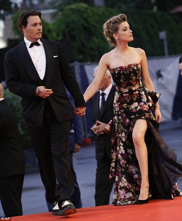 Stunning: With her flawless figure on full display, Amber stunned in floral dress that had a thigh-baring split, as she smiled proudly beside her A-Lister husband