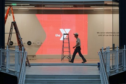 A construction worker walked past the YMCA's glowing logo in the main entrance area.
