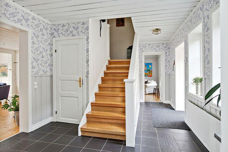 Hall med tåligt klinker golv och trappan leder upp till övervåningen
