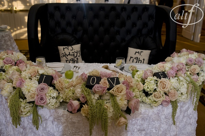 White hydrenga, faith roses, green hanging ameranthus, and sahara roses for the sweetheart table. Black leather high backed couch as the seating. #naakiti #altf #fourseasons