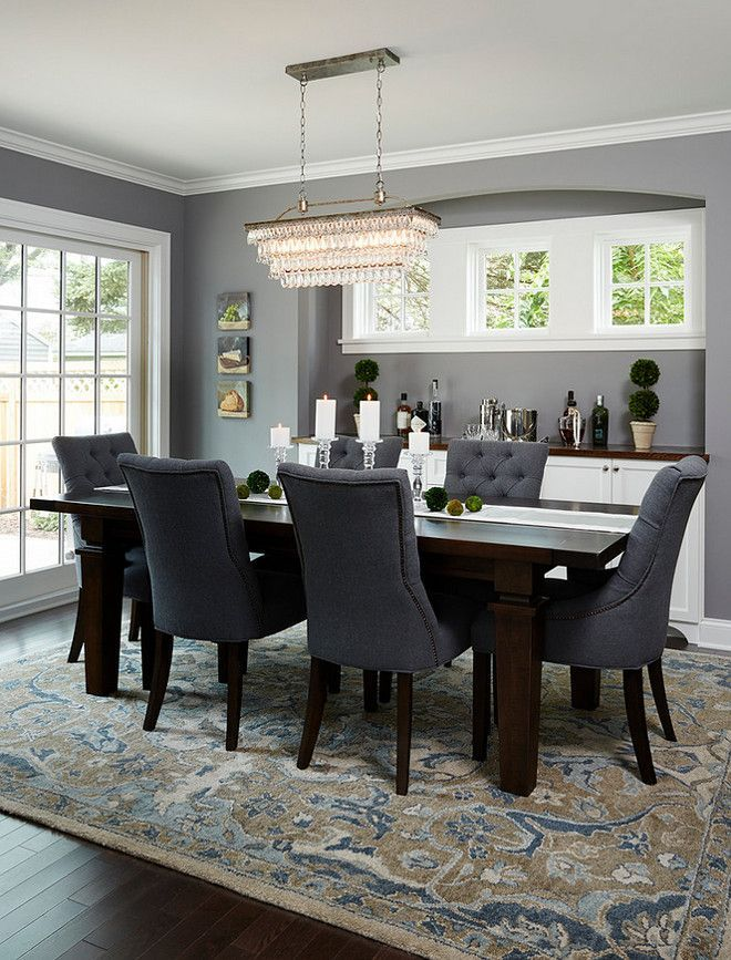 Dining Room With Dark Wood Floors, Beautiful Patterned Rug And Blue Chairs  And Dark Wood