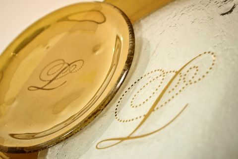 Custom designed dinnerware set with glass show plate and bread and butter plate in gold. By Glass Studio