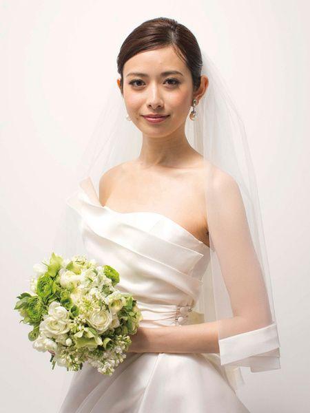ドレスの胸もとに施された立体的なデザインは、上半身を美しい存在感で彩ります。シンプルなシニヨンヘアにサテン地でパイピングしたベールを合わせる...