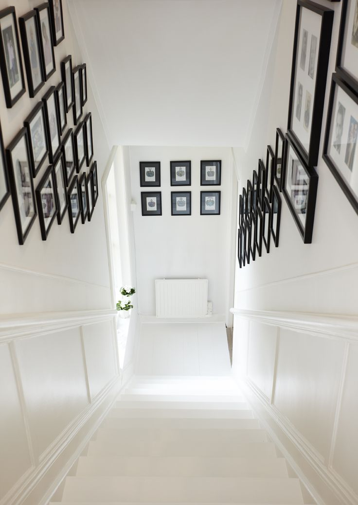 The white-painted staircase adorned with framed photographs and paintings. lijkt me leuk idee voor in huis