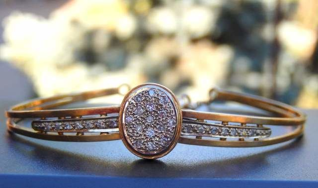 Draaibare armband met kleine ruitjes in 18 kt goud.  Antieke bangle type armband met weinig beveiliging ketting in 18 kt geel goud.Tweedehands in zeer goede staat. Hand gemaakt door een kunstenaar. Met de verschillende kenmerken van de adelaar.Centrale patroon van 13 x 10 mm bezaaid met 15 kleine diamanten van 1.2 tot 1.35 mm elk in een briljante knippen.Breedte van de zijden is 6 mm met de centrale patroon ook versierd met diamanten van 15 mm met rand in witgoud.29 briljant-cut diamant…