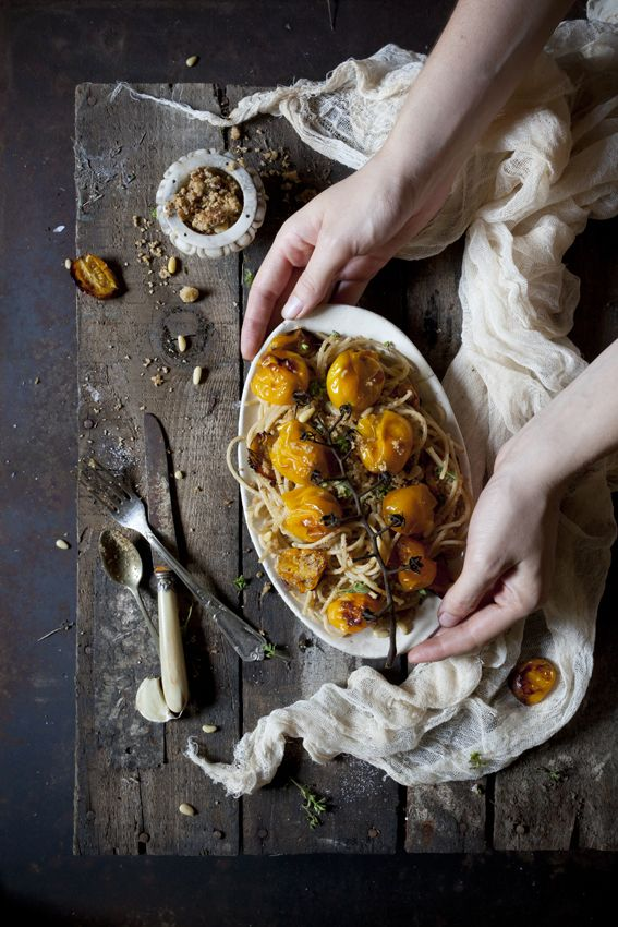 person serving a oval-shape plate of spaghetti with roasted yellow tomatoes on a rustic table