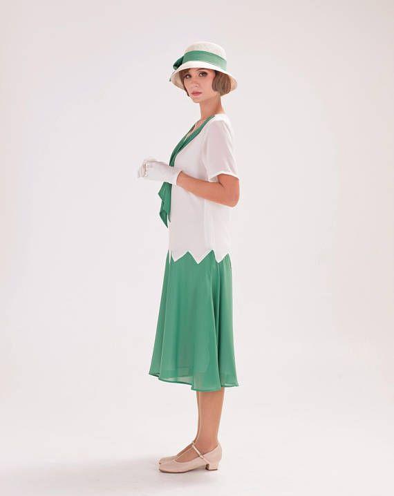 Este bonito vestido de los años 1920 zig zag está hecho de tela de gasa en blanco roto y verde mar. Cuenta con una costura de zig zag conectando el corpiño y la falda, que era un estilo popular en los años 20. El vestido viene con mangas cortas y escote redondo, decorado con un