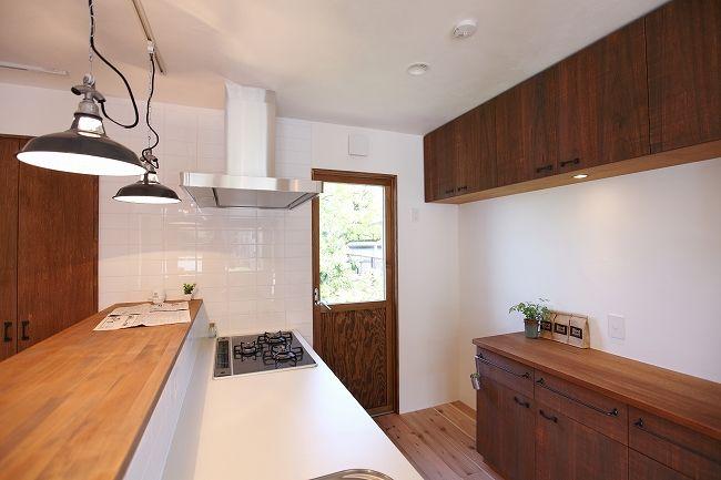 玄関ホールから自然の明かりが優しく差し込む、一階のワンフロアー(LDK)。 シンプルな木製ドアと、漆喰の素材感、そして 無垢の秋田杉の床...素...