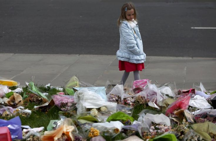 A young girl looks at the tributes to PC Palmer at Westminster ahead of his funeral today