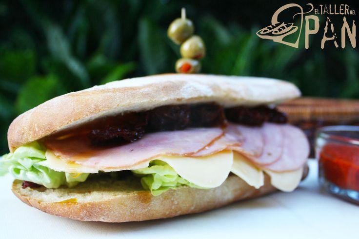 Sándwich en pan ciabatta, con jamón, queso provolone, lechuga, tomates secos y aceitunas
