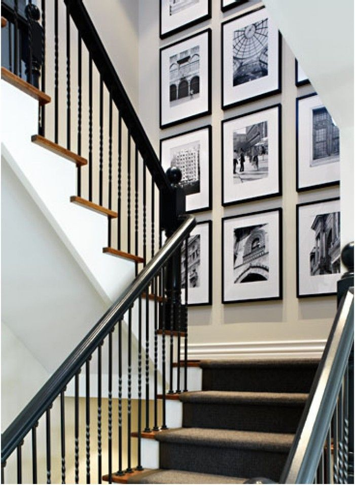 Black railing - hides dirty hands. Wood steps - hides dirty feet. White/light cream walls. black picture frames in grid pattern with white matte
