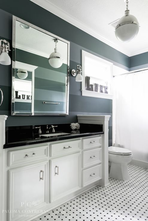 Striped kids' bathroom features tone-on-tone, black walls as backdrop for polished nickel, rivet mirror flanked by white glass sconces over extra-long vanity topped with Absolute Black Granite  countertop illuminated by Hicks Pendant in Polished Nickel.