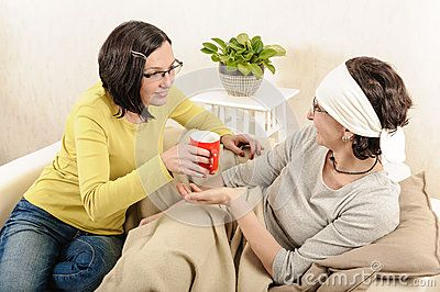 Beautiful young woman giving cup of tea sick flu friend, smiling, indoor.