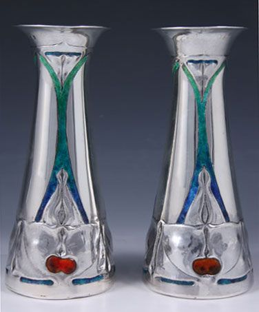 Manufacturer Liberty & Co. Designer Archibald Knox Description Pair of stunning silver Arts & Crafts vases with enamel decoration. Country of Manufacture England Date 1904