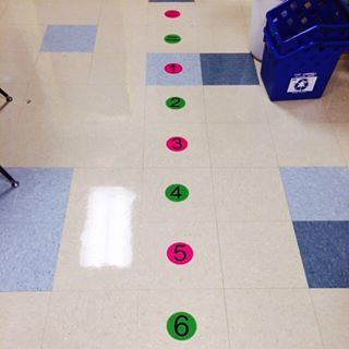 """Eliminate door crowding by adding """"line up"""" stickers to your floor. 