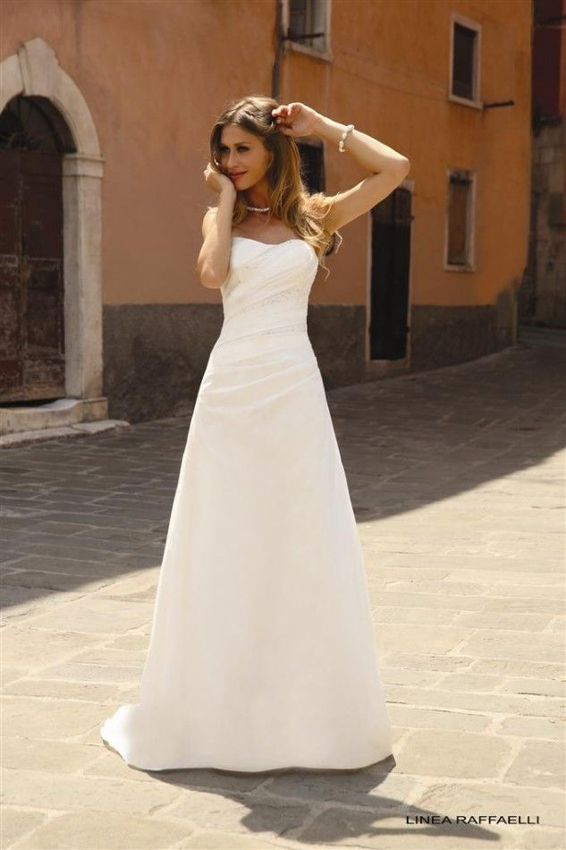 Linea Raffaelli 150-033-01, collectie 2015 Een eenvoudige trouwjurk gemaakt van de mooiste zijde. Deze strapless jurk heeft een kort sleepje. Koonings kan jurken vaak afstemmen naar de wensen van de bruid.