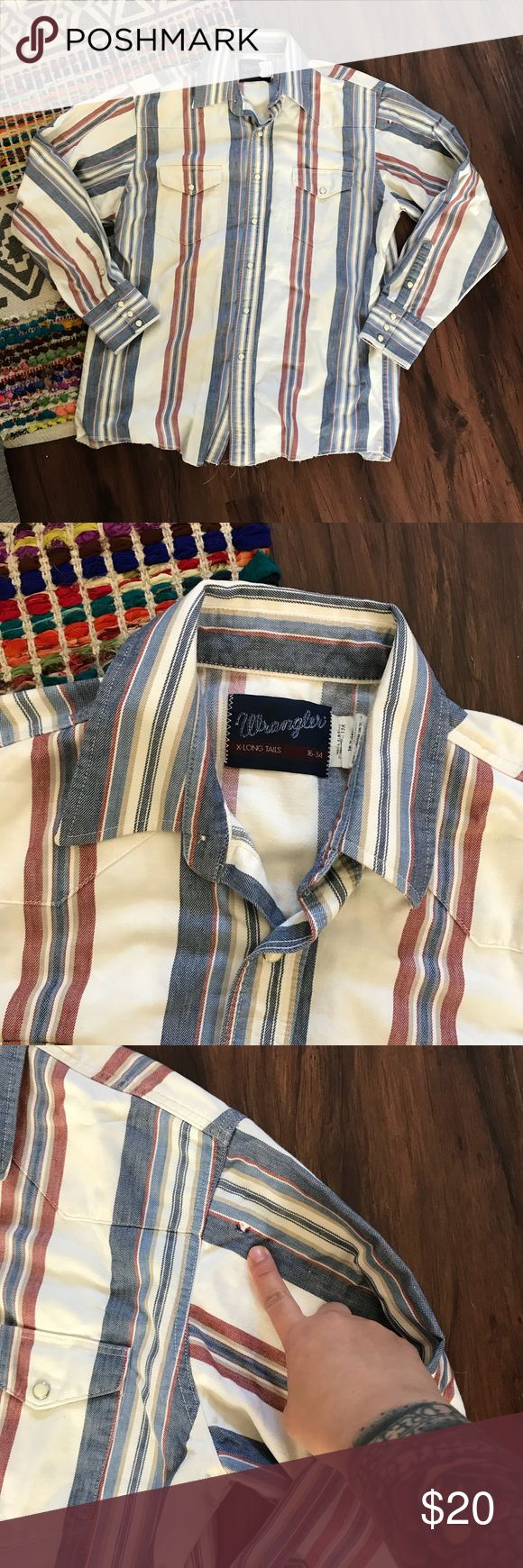 """Vintage Wrangler Cowboy Cut Western Button Up Vintage Wrangler Western cowboy cut button down shirt. Pearlized snap buttons on sleeves, breast pockets and down the front. Only flaw is a small tear and faint spot below left breast pocket as pointed out in photo. Other than that this is in excellent vintage condition. This is a """"long tail"""" meaning the back is cut longer than the front. Fits like an XL but refer to measurements for proper fit. Bust 23"""" // waist 22.5"""" // length 30"""" back 33""""…"""