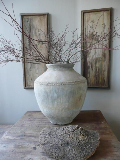 natural palette...beautiful shaped large vase, with branches, on a worn wood table...