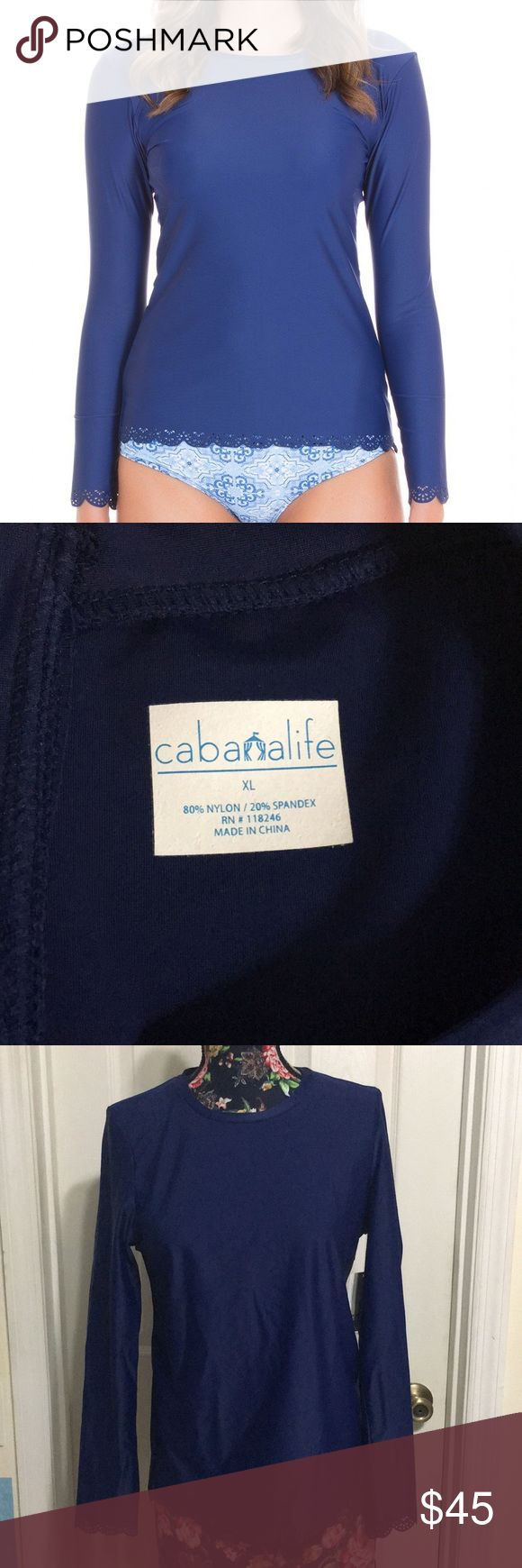"""Cabana Life Scalloped Rashguard Take on the waves or the closest cabana chair in this rash guard from Cabana Life! Navy blue long sleeve rash guard with scalloped hem and cuffs, zips up back. Features 50+ UV protection, blocks 98% UVA and UVB rays. Size L, NWT, never worn. Cover photo courtesy of cabanalife.com.  Measures approximately: Bust: 40"""" Torso: 36"""" Length: 25"""" Sleeve Length: 25""""  🚫TRADES🚫 🚫OFFLINE TRANSACTIONS🚫  ✅BUNDLES✅ ✅REASONABLE OFFERS✅  Happy Poshing! 😄 Cabana Life Swim"""