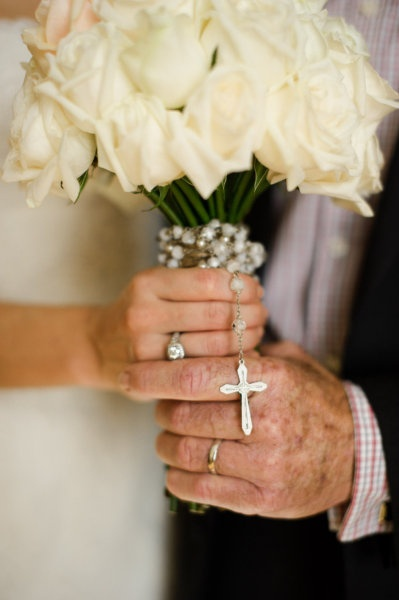 Photo of bouquet being held by the bride and her father