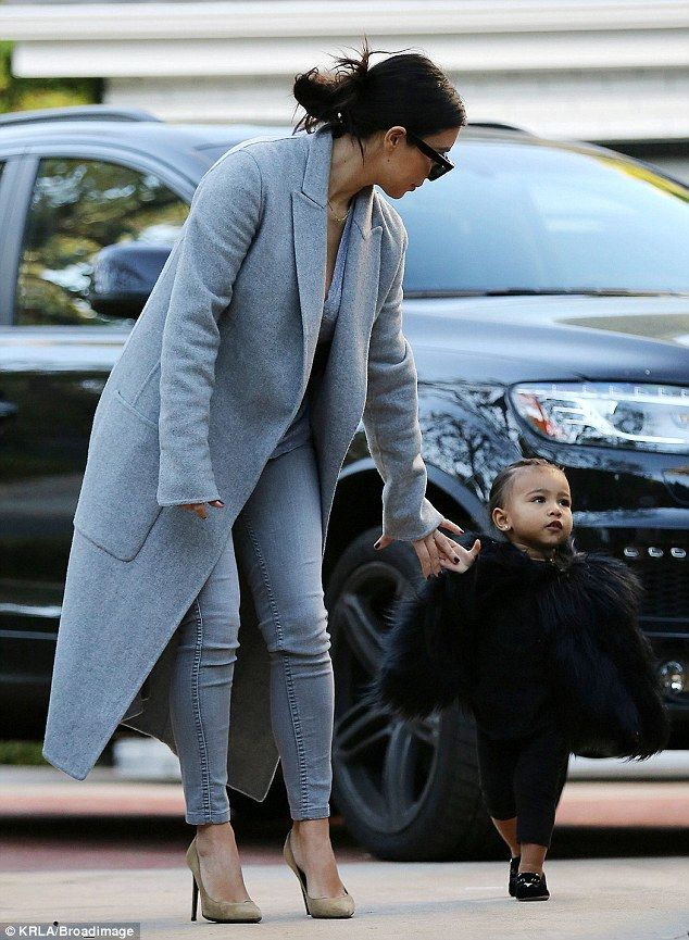 Doting mom: Kim was seen reaching down to grab hold of the tot's hand
