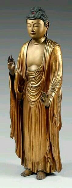 Large gold lacquered wooden statue of standing Buddha, eyes half-closed, wearing a thin draped dress, hands in vitarka mudra position.