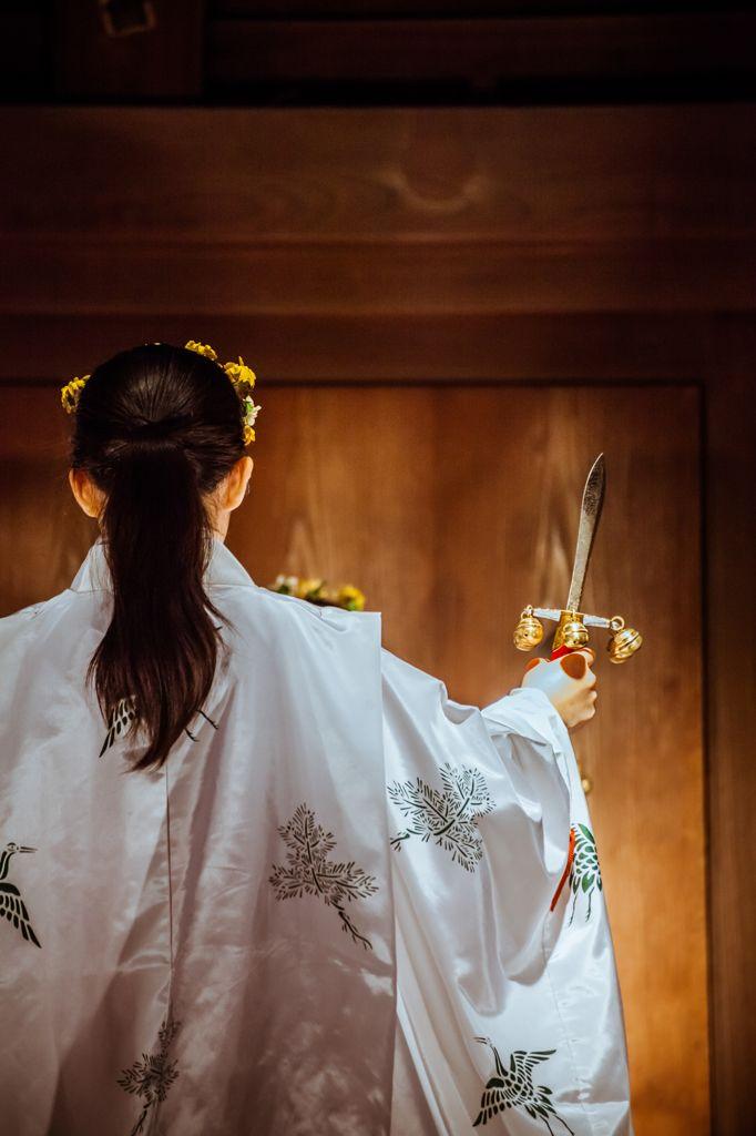 A miko (巫女), Shinto shrine maiden, dancing kagura.