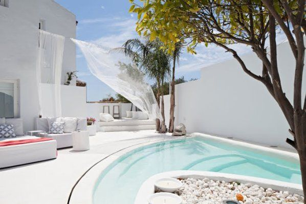 Villa Mandarina, con ese blanco impoluto que resplandece bajo el sol marbellí. La piscina escalonada invita a refrescarse en esas aguas levemente azuladas. La cortina de tul mecida por la brisa le da un encantador movimiento a toda la imagen