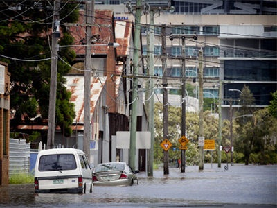 Partly submerged cars sit stranded along a street in the inner Brisbane suburb of Newmarket on 27 January, 2013.