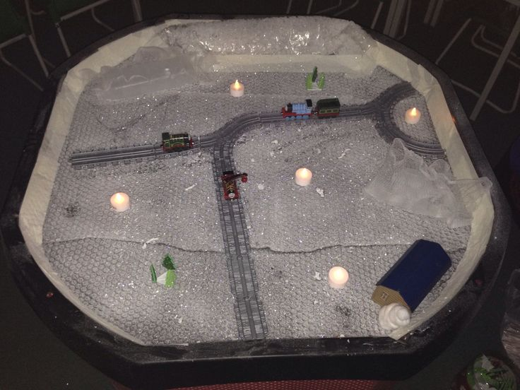 Tuff Spot Snow Scene. Bubble wrap snow, LED candles, glittery Christmas trees and a railway track. #tuffspot #tufftray