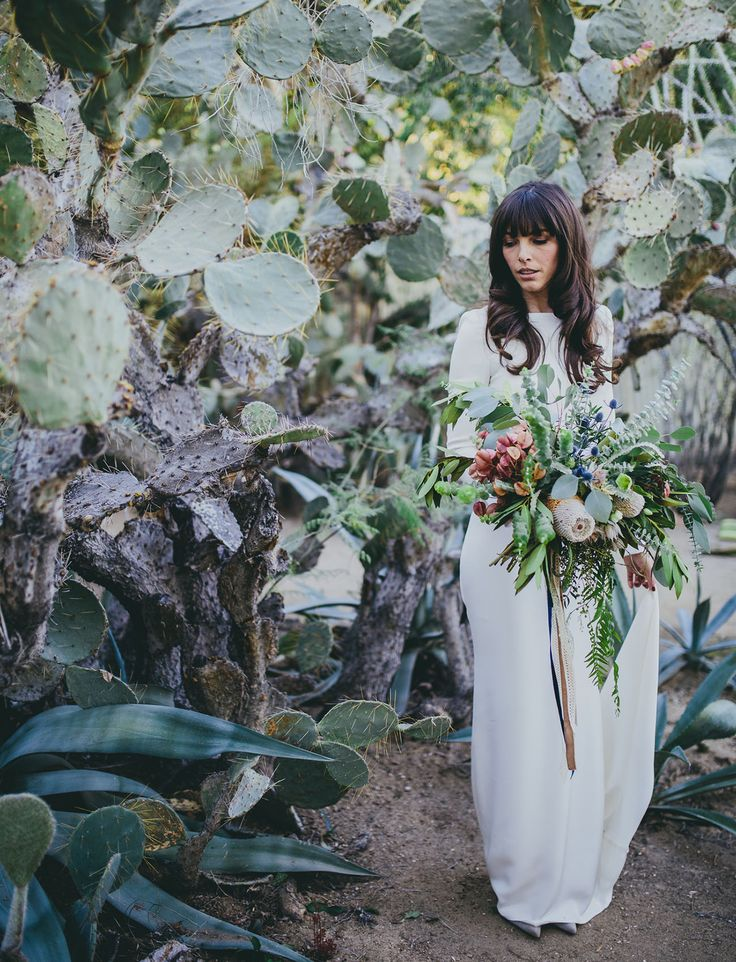 This drop dead gorgeous Houghton Dress is both minimalistic and super modern. We love the addition of the cactus background and the abundant florals! This bride's style is super chic + elegant, especially the relaxed curls in her hair and heavy fringe/bangs. Parisian elegance meets California cool