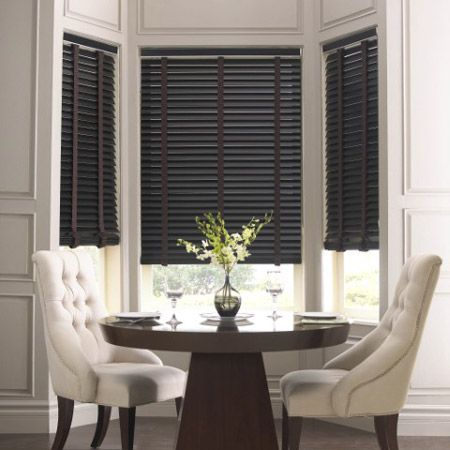 I like the contrast of the dark blinds with the white chairs.