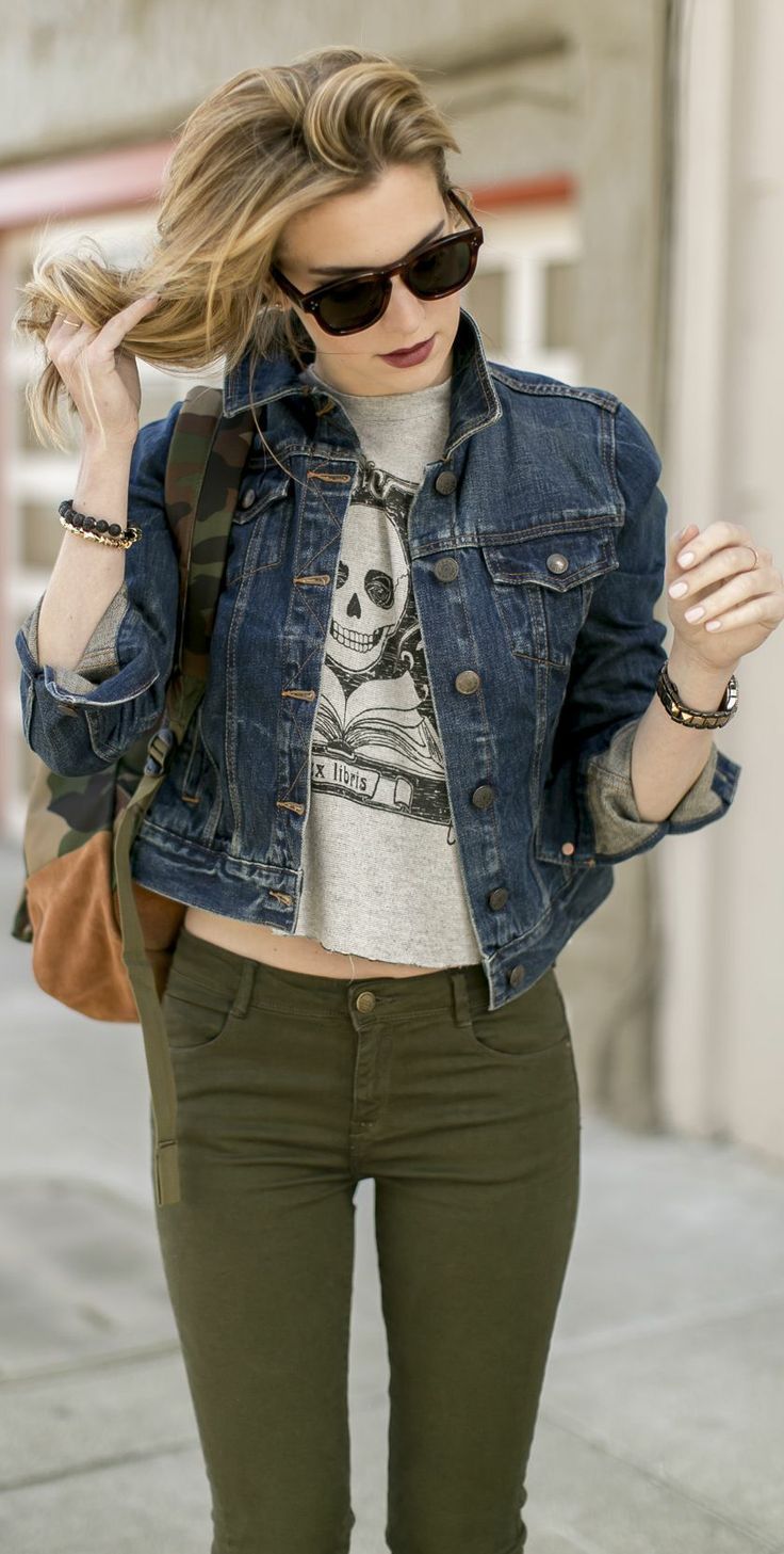 Rock a navy blue denim jacket with army green skinny jeans for a comfortable outfit that's also put together nicely.  Shop this look for $44:  http://lookastic.com/women/looks/skinny-jeans-backpack-denim-jacket-cropped-top-sunglasses/5749  — Olive Skinny Jeans  — Olive Camouflage Backpack  — Navy Denim Jacket  — Grey Print Cropped Top  — Dark Brown Sunglasses