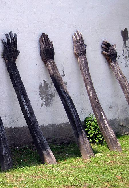 Vigas de madera con la extremidad en forma de mano apoyadas en un muro exterior