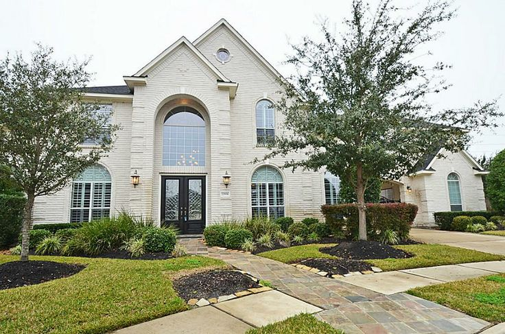 Slate walkway, double door entry, arched windows, plantation shutters.