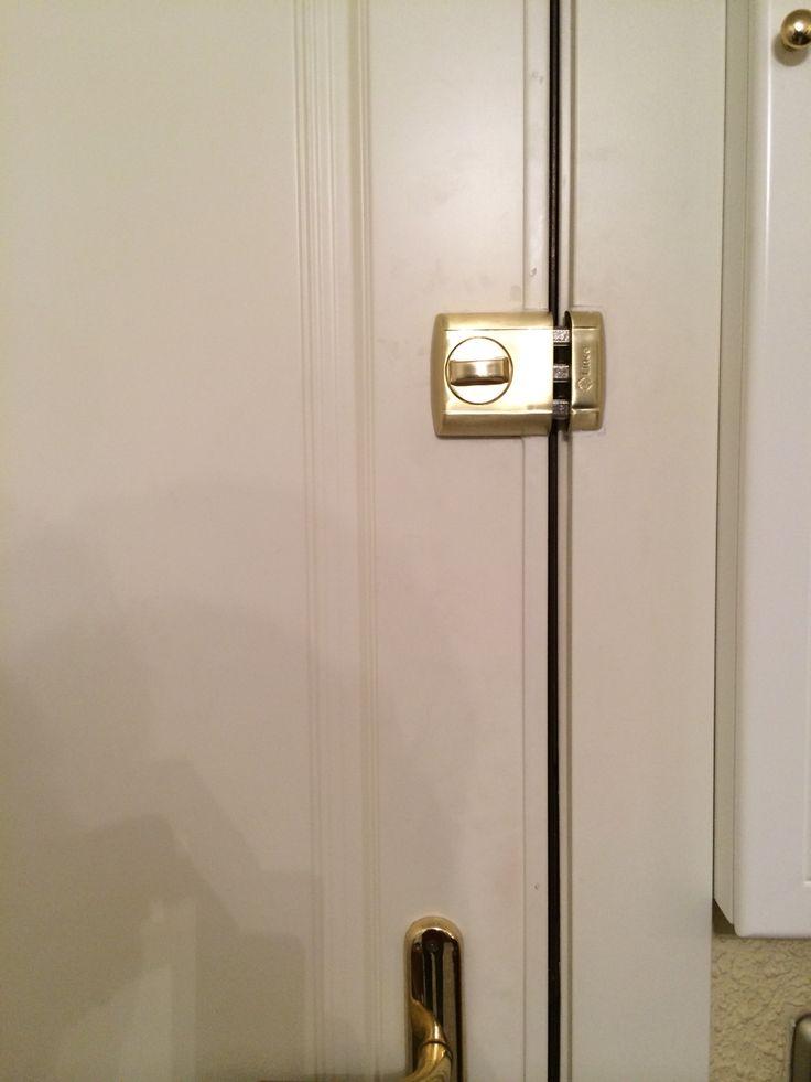 Cerrojo de seguridad marca Lince en color dorado. Instalado en una puerta blindada con panel lacado en blanco.