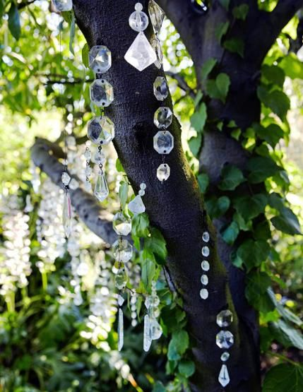 Lovely way to repurpose parts of an old chandelier in a garden.  Beautiful in the morning sun, and LED lights give prisms a bluish cast that is magical in the evening ...