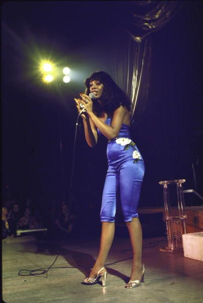 Singer Donna Summer performing on stage wearing electric blue outfit