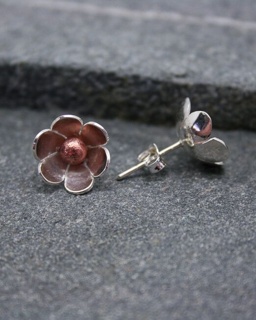 Silver daisy stud earrings with copper centres and silver posts and scrolls.  Created by hand in our Porthleven studio.  The 12mm. daisies have been hand saw pierced from silver sheet, domed and completed with a single copper bead to the centre.  We can also create these earrings in mixed coloured gold.  Please get in contact for an estimate.    #Bridal #Daisy #Earrings #HandmadeJewellery #MixedMetal #Silver #Starboard #Wedding