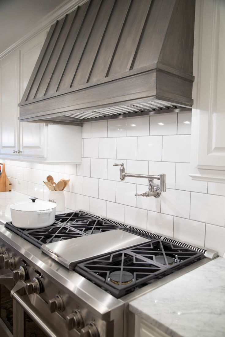 Delightful ... With Carrera Marble Countertops And Large Subway Tiled Backsplash Flank  Stained Wood Hood Paired With Swing Arm Pot Filler And Stainless Steel  Stove. Great Ideas