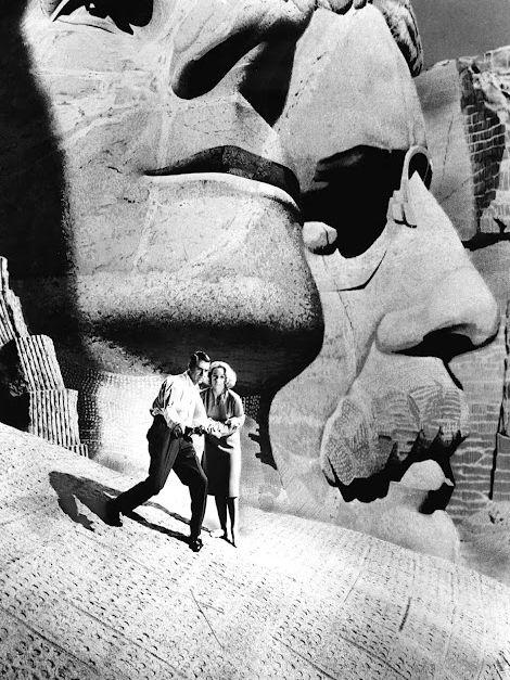 NORTH BY NORTHWEST (1959) - Cary Grant & Eva Marie Saint encounter danger at Mount Rushmore in South Dakota - Directed by Alfred Hitchcock - MGM - Publicity Still.