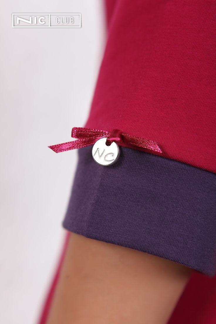 Домашнее платье Ciliegia («Чильеджа») от Nic Club скроено из высококачественного трикотажа средней плотности, полуприлегающего силуэта, с рукавами длиной ¾. Окантовка круглой горловины и манжеты рукавов, а также оборка по низу платья выполнены из контрастной ткани. Небольшой принт на правой стороне груди придает изделию яркий акцент. Манжет одного рукава украшен атласным бантом и серебристым аксессуаром с логотипом NC, а спинка — декоративной планкой с пуговицами.