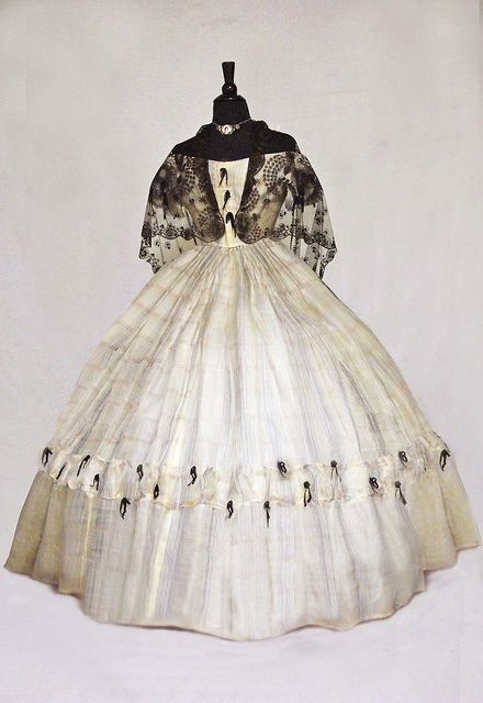 White gauze ball gown with black lace and ribbon knot decoration, 1860.- this is a repin from a Flickr account, so I can't verify if it is an original garment. It does look like it though.